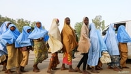 Girls who were kidnapped from a boarding school in the northwest Nigerian state of Zamfara walk in line after their release, in…