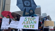 People hold placards as they gather to protest against anti-Asian hate crimes, racism and vandalism, outside City Hall in…