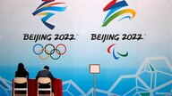 Staff members sit near a board with signs of the 2022 Olympic Winter Games, at the National Aquatics Center, known colloquially…
