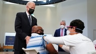U.S. President Joe Biden puts his hand on a man's shoulder during a visit to a coronavirus disease (COVID-19) vaccination site…