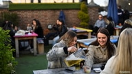 People enjoy a drink at the Skylight rooftop bar as the coronavirus disease (COVID-19) restrictions ease, in London, Britain.