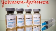 "FILE - Vials with a sticker reading, ""COVID-19 / Coronavirus vaccine / Injection only"" and a medical syringe are seen."