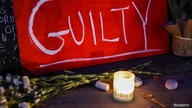 "A sign reading ""GUILTY"" rests next to a candle at Carl Schurz Park after the verdict in the trial of former police officer…"