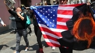 Protesters against Peruvian President Martin Vizcarra, who faces an impeachment vote, carry a U.S. flag with the letter Q,…