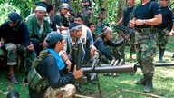 FILE - In this undated file photo, Abu Sayyaf spokesman Abu Sabaya, right foreground, is seen with his band of armed extremists…