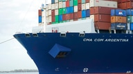 Crew members stand on the bow as the CMA CGM Argentina arrives at PortMiami, the largest container ship to call at a Florida…