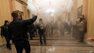 FILE - In this Jan. 6, 2021, file photo, smoke fills the walkway outside the Senate Chamber as violent rioters loyal to…
