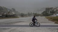 A man rides his bicycle past fields covered with volcanic ash a day after the La Soufriere volcano erupted, in Kingstown, on…