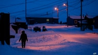 FILE - In this Jan. 20, 2020, file photo, a woman walks before dawn in Toksook Bay, Alaska, a mostly Yuip'ik village on the…