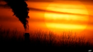 FILE - Emissions from a coal-fired power plant are silhouetted against the setting sun.