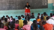 FILE - A teacher talks with a student at a class in a primary school in Nkhatabay district in northen Malawi. (Lameck Masina/VOA)