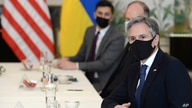 FILE - U.S. Secretary of State Antony Blinken, right, waits for the start of a meeting with Ukrainian Foreign Minister Dmytro Kuleba (seated opposite; not pictured), in Brussels, April 13, 2021. Blinken is due to meet with Kuleba in Kyiv next week.