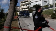 A police truck carries the car of a veteran Greek crime reporter in southern Athens, April 9, 2021.