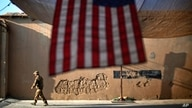 FILE - A U.S. soldier walks past an American flag hanging in preparation for a ceremony marking the tenth anniversary of the 9/11 attacks, at Forward Operating Base Bostick, in Kunar province, Afghanistan, Sept. 11, 2011.