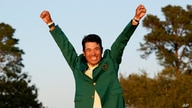 Hideki Matsuyama, of Japan, celebrates wearing the champion's green jacket after winning the Masters golf tournament, in Augusta, Georgia, April 11, 2021.