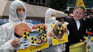 Environmental activists wearing a mask of Japanese Prime Minister Yoshihide Suga and protective suits perform to denounce the Japanese government's decision on Fukushima water, near the Japanese embassy in Seoul, South Korea, April 13, 2021.