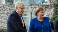 FILE - German Chancellor Angela Merkel, right, greets Britain's Prime Minister Boris Johnson upon his arrival to attend the peace summit on Libya at the Chancellery in Berlin, January 19, 2020.