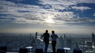 Two men enjoy the city skyline view on the 314-meter high rooftop terrace of the Mahanakhon building in Bangkok on November 11,…