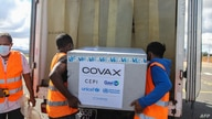 Workers load boxes of Oxford/AstraZeneca Covid-19 vaccines, part of the the Covax programme, which aims to ensure equitable…
