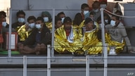 Migrants warmed by emergency blankets arrive on a boat of the Italian Guardia Di Finanza law enforcement agency on May 17, 2021…