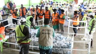 Officials stand around ballots in Buka, Bougainville, Papua New Guinea, December 9, 2019. Picture taken December 9, 2019…