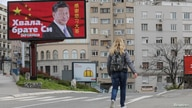 A woman passes by a billboard depicting Chinese President Xi Jinping as the spread of the coronavirus disease (COVID-19)…