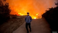 FILE - A man walks away from the Blue Ridge Fire burning in Yorba Linda, California, U.S., October 26, 2020.
