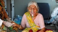 Lilaben Gautambhai Modi, 80, wearing an oxygen mask, sits inside an ambulance as she waits to enter a COVID-19 hospital.
