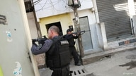Policemen aim their weapons during an operation against drug dealers in Jacarezinho slum in Rio de Janeiro, Brazil May 6, 2021…