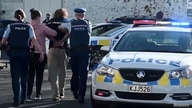Police officers detain a man after a stabbing incident at the Countdown supermarket, in Dunedin, New Zealand, May 10, 2021 in this screen grab taken from video.