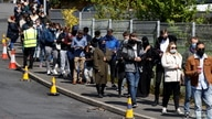 People line up outside a mobile vaccination centre, amid the outbreak of the coronavirus disease (COVID-19) in Bolton, Britain,…