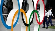 Security personnel stand guard near the Olympic rings monument during a rally by anti-Olympics protesters outside the Japanese…