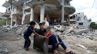 Palestinians sit on chair amid the rubble of a building which was damaged in Israeli air strikes during the Israel-Hamas fighting in Gaza May 23, 2021.