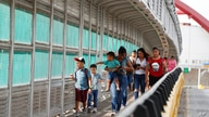 FILE - In this June 28, 2019 file photo, local residents with visas walk across the Puerta Mexico international bridge to enter…