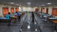 Indian workers disinfect an isolation center for COVID-19 positive people in Hyderabad, India, May 3, 2021.