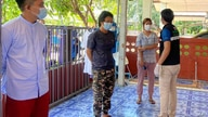 In this photo released by the San Sai District Administrative Office, a Thai officer checks the temperature of journalists…