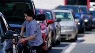 A customer pumps gas at Costco, as others wait in line, on Tuesday, May 11, 2021, in Charlotte, N.C. Gasoline futures are…