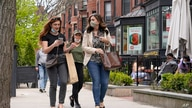 FILE - Pedestrians walk along Boston's fashionable Newbury Street in Massachusetts.