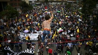 A tight rope artist stands over demonstrators as they march during an anti-government protest in Bogota, Colombia, Wednesday,…