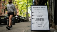 A pedestrian passes a storefront sign that lists COVID-19 protective protocols required for entry in the retail shopping district of the SoHo neighborhood of the Manhattan borough of New York, May 14, 2021.