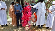 Indian Christian priests and others throw flower petals on the grave of Father Rolfie D'Souza's who died of COVID-19 after his…