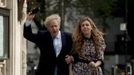 British Prime Minister Boris Johnson arrives at a polling station with his partner Carrie Symonds to cast his vote in local council elections, in London, May 6, 2021.