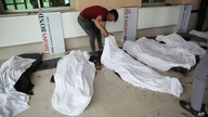 A young man try to identify dead bodies at a hospital after a bomb explosion near a school west of Kabul, Afghanistan, May 8, 2021.
