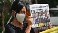 A supporter of two executives from Hong Kong's pro-democracy Apple Daily newspaper, chief editor Ryan Law and CEO Cheung Kim…