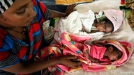 FILE - An Ethiopian woman who fled the ongoing fighting in Tigray region, nurses her newly born children inside a clinic in the Hamdayat camp on the Sudan-Ethiopia border, in eastern Kassala state, Sudan, Dec. 15, 2020.