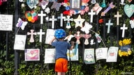 """A child looks at the """"Naming the Lost Memorials,"""" as the U.S. deaths from the coronavirus disease (COVID-19) are expected to…"""