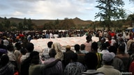 FILE - People stand in line to receive food donations, at the Tsehaye primary school, which was turned into a temporary shelter for people displaced by conflict, in the town of Shire, Tigray region, Ethiopia, March 15, 2021.