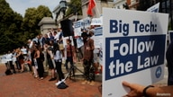 """A man holds a sign reading """"Big Tech Follow the Law"""" at a demonstration opposing a ballot campaign by companies such has Uber,…"""