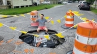 New Orleanian Joe Frisard sits beside a massive pothole two blocks from his home. Residents are no strangers to potholes, often decorating them or making jokes -- as was the case when an unknown person placed a miniature car inside this one.