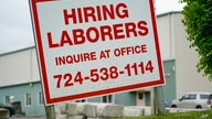 FILE - A sign seeking to hire laborers is posted outside a concrete products company in Evans City, Pennsylvania, May 5, 2021.